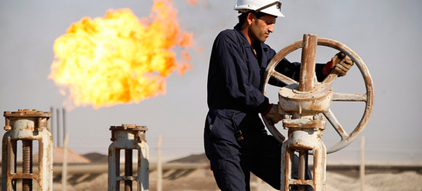 A worker adjusts the valve of an oil pipe at West Qurna oilfield in Iraq in 2010. Exxon Mobil is lobbying other American oil producers to support a revenue-neutral carbon tax. (photo: Atef Hassan/Reuters)