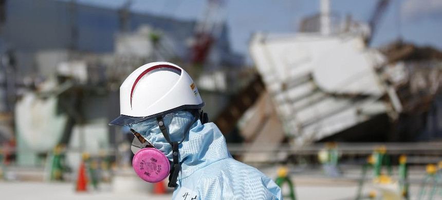 A Tokyo Electric Power Co. (TEPCO) employee, wearing a protective suit and a mask, walks in front of the No. 1 reactor building at TEPCO's Fukushima Daiichi nuclear power plant. (photo: Toru Hanai/Bloomberg)