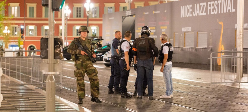 Police officers and a soldier stand by the sealed off area of an attack after a truck drove on to the sidewalk and plowed through a crowd of revelers who'd gathered to watch the fireworks in the French resort city of Nice, southern France, Friday, July 15, 2016. (photo: Ciaran Fahey/AP)