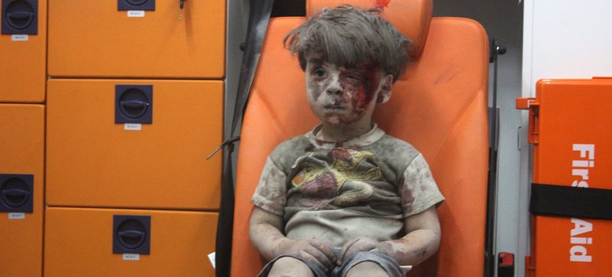 A 5-year-old boy, identified in news reports as Omran Daqneesh, sits in an ambulance Wednesday after reportedly being pulled out of a building hit by an airstrike in Aleppo, Syria. (photo: Amhmoud Rasian/Anadolu/Getty)