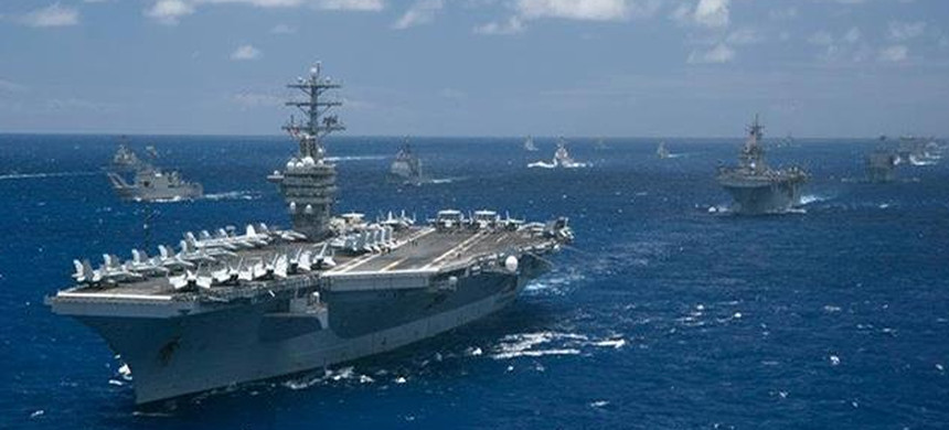 US aircraft carrier with carrier battle group behind. (photo: US Navy)