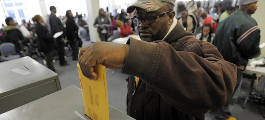 Andre Witcher, of Detroit, casts his ballot at the Wayne County Community College Northwest Campus. (photo: AP)