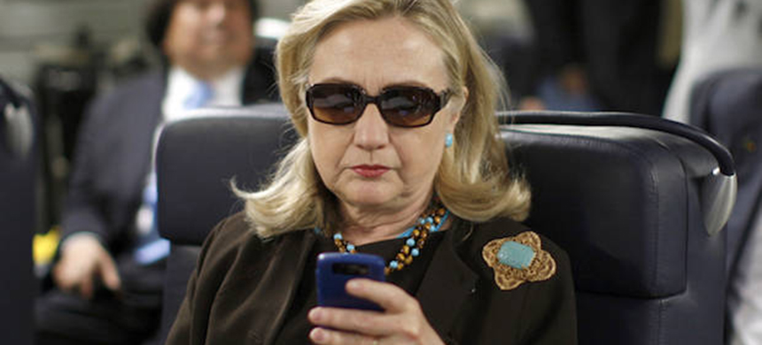 Secretary of State Hillary Clinton checks her phone on October 18, 2011. (photo: Kevin Lamarque/Reuters)