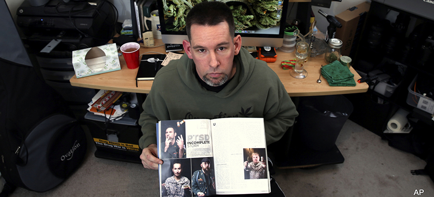 Former U.S. Marine Mike Whiter, who uses marijuana to treat post-traumatic stress disorder, displays some of his photographs of military personnel published in a magazine, as he sits at a desk in his home in Philadelphia. (photo: AP)
