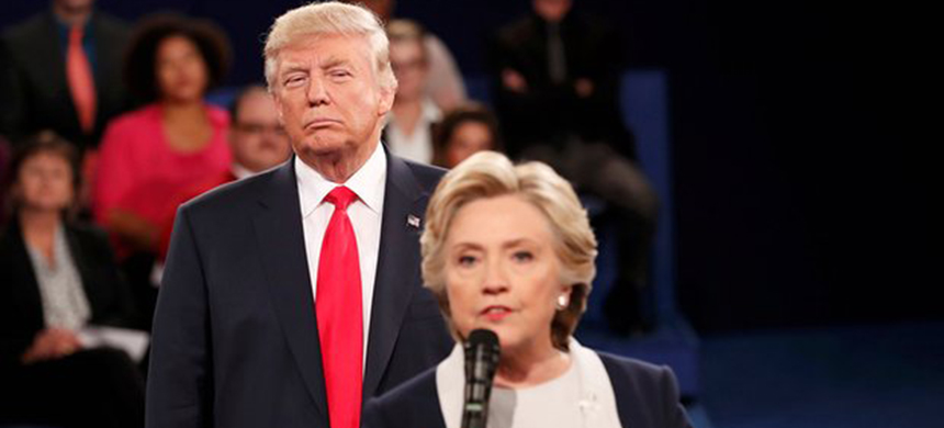Donald Trump lurks behind Hillary Clinton as she answers a question from the audience. (photo: Rick Wilking/Reuters)