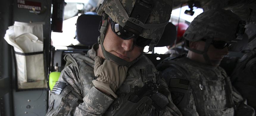 The Pentagon is seeking millions of dollars from nearly 10,000 current or former soldiers in the California National Guard, saying they weren't eligible for re-enlistment bonuses. Here, soldiers from the state's guard force are seen in 2010, resting during transport in northeastern Afghanistan. (photo: Brennan Linsley/AP)