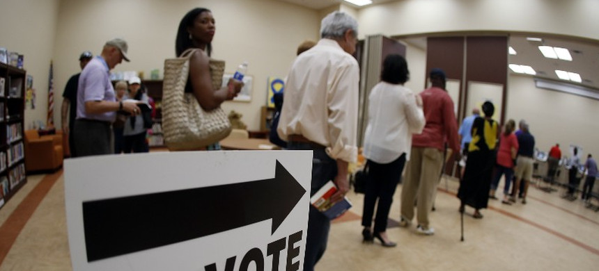 Voters stand in line at a polling station. (photo: John Bazemore/AP)