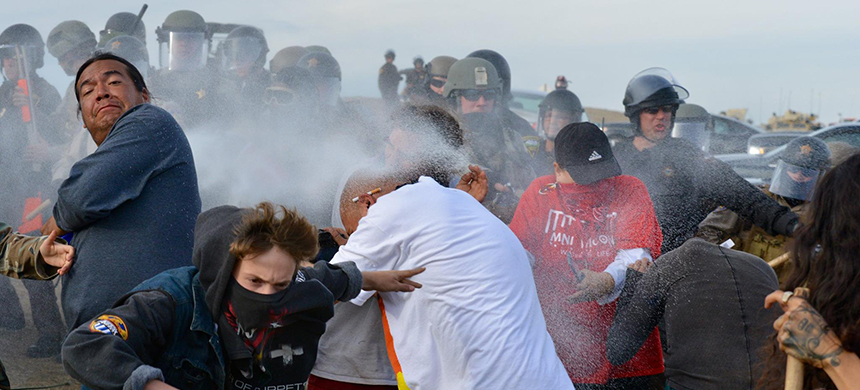 Security forces protecting the Dakota Access pipeline construction spray protesters with pepper spray. (photo: Tim Yakaitis)