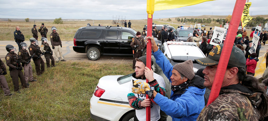 Dakota Access Pipeline protesters facing police officers in North Dakota this month. (photo: Terray Sylvester/Reuters)