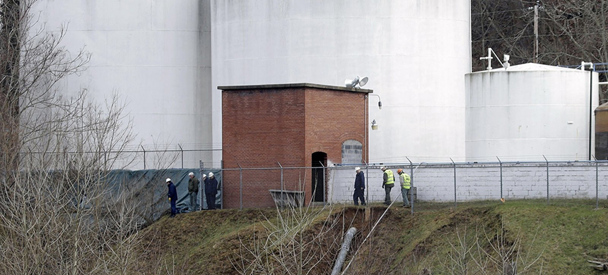 Workers inspect an area around storage tanks where a chemical leaked into the Elk River at Freedom Industries' storage facility in Charleston, W.Va., in January 2014. (photo: Steve Helber/AP)