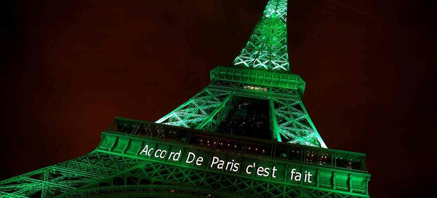 The Eiffel Tower is illuminated in green with the words 'Paris Agreement is done', to celebrate the Paris climate change agreement. (photo: Jacky Naegelen/Reuters)