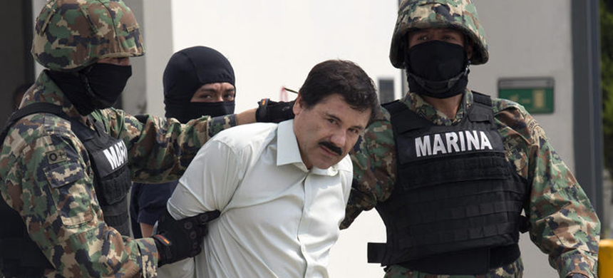 Drug trafficker Joaquin 'El Chapo' Guzman is escorted to a helicopter by Mexican security forces at Mexico's International Airport in Mexico City on Feb. 22. (photo: Susana Gonzalez/Bloomberg)