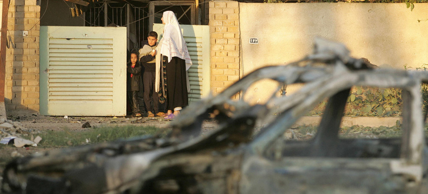 An Iraqi family looks out the front gate of their home following a car bomb on Nov. 19, 2004, in Baghdad. (photo: Marwan Naamani/Getty)