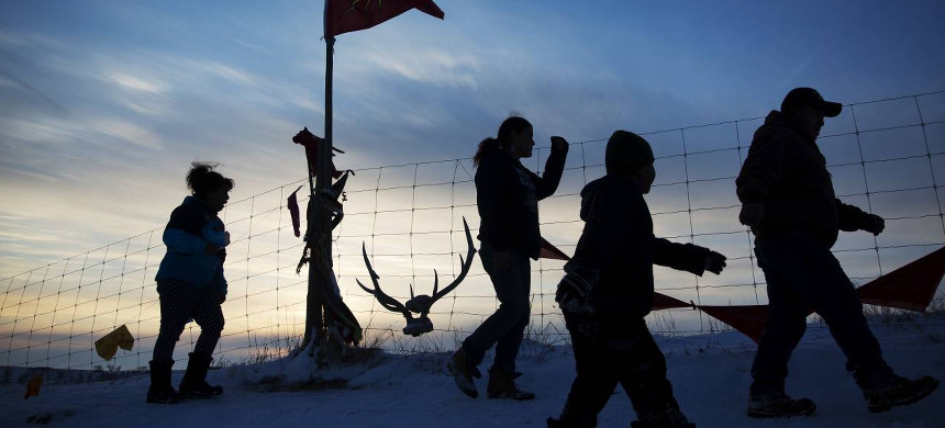 Water Protectors in front of a sunset at Standing Rock. (photo: AP)
