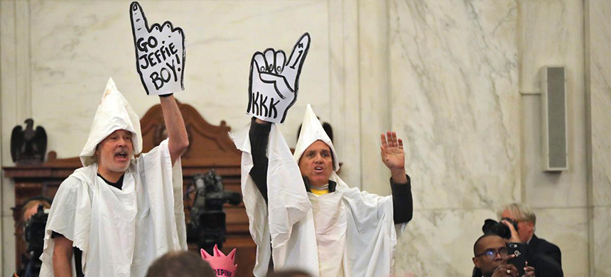 Men dressed up as KKK members jumped out of their seats at Senator Jeff Sessions' Attorney General confirmation hearing. (photo: Andrew Harnik/AP)