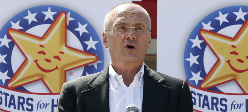 Andrew Puzder has in the past defended his company's notorious advertising that often features scantily clad women eating burgers, saying 'ugly ones don't sell burgers.' (photo: AP)