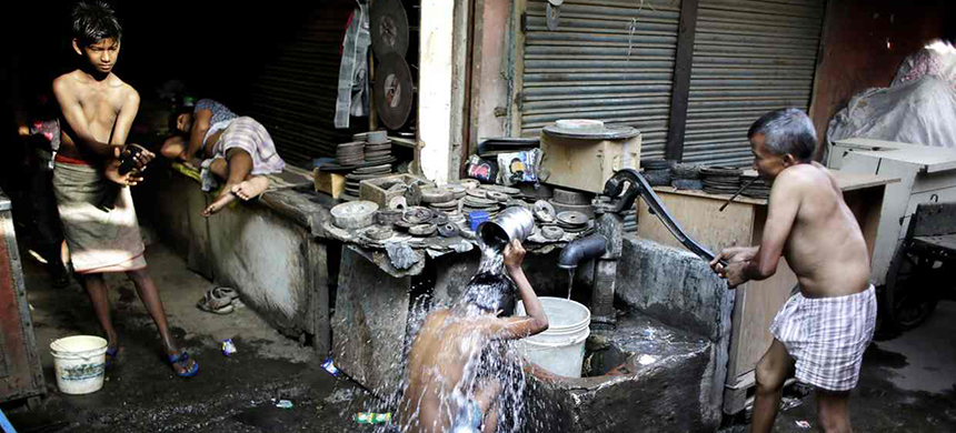 Indian migrant daily wage workers bath at a public well in New Delhi. New information shows that poverty in China and India is worse than previously thought. (photo: Altaf Qadri/AP)