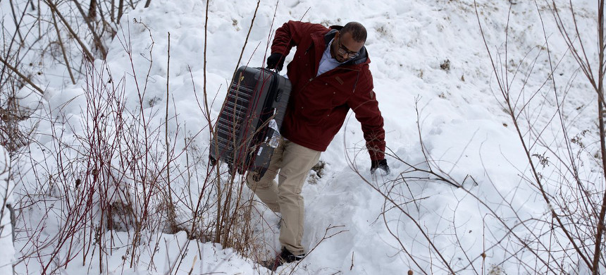 Man carries his suitcase across the U.S./Canada border. (photo: Christinna Muschi/Reuters)