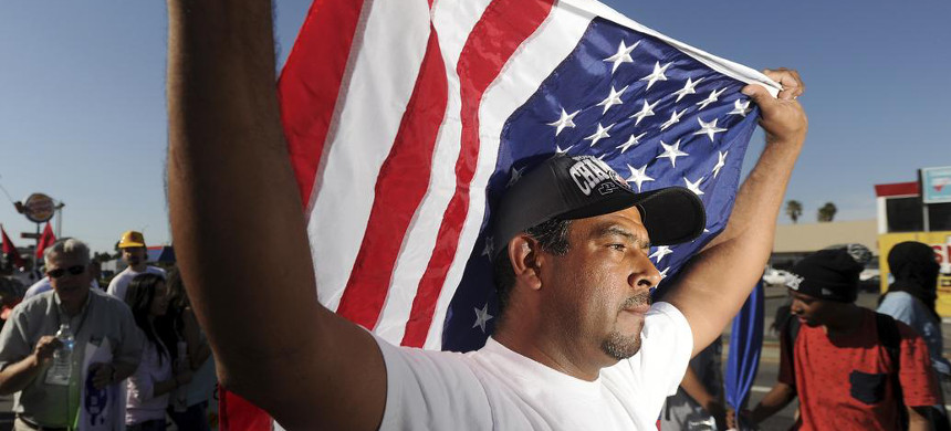 A man holds an American flag at a rally. (photo: Noah Berger/Reuters)