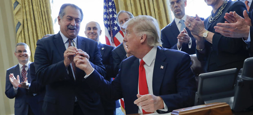 President Donald Trump gives the pen he used to sign the executive order on regulations to Dow Chemical president, chairman and CEO Andrew Liveris, as other business leaders applaud in the Oval Office. (photo: Pablo Martinez Monsivais/AP)
