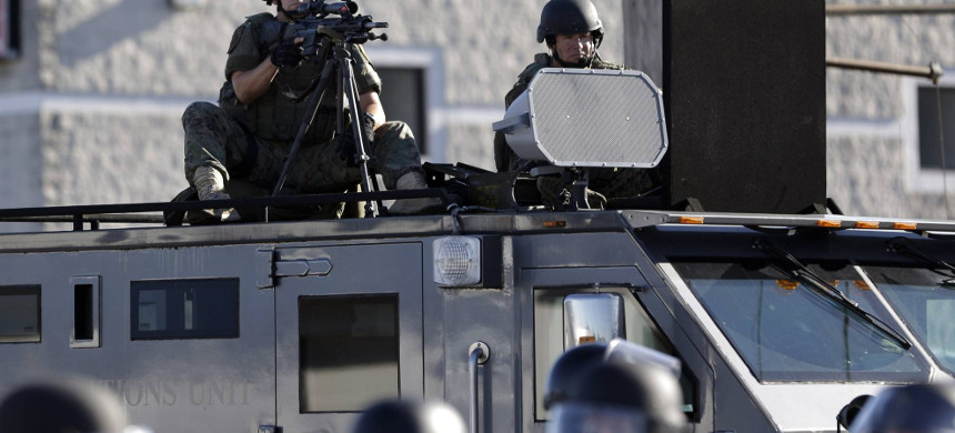 Police move to disperse protesters in 2014. The Obama administration issued an order that banned local police from acquiring military-style gear; President Donald Trump, as a candidate, vowed to reverse the order, and police groups are expecting him to do it. (photo: Jeff Roberson/AP)