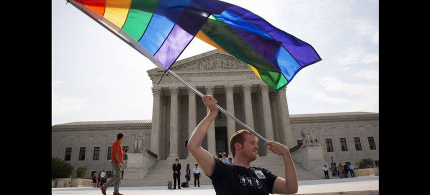 In a June 25, 2015 photo, John Becker, 30, of Silver Spring, Md., waves a rainbow flag in support of gay marriage outside of the Supreme Court in Washington. (photo: Jacquelyn Martin/AP)