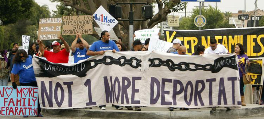 Immigration groups holding signs against deportation as part of a protest in Los Angeles in 2013. (photo: LA Times)