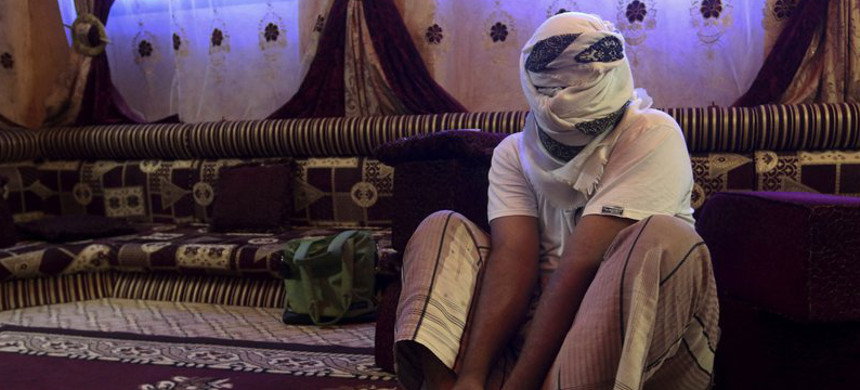 Yemeni demonstrates how he was bound while held in a secret prison in Yemen. (photo: AP)