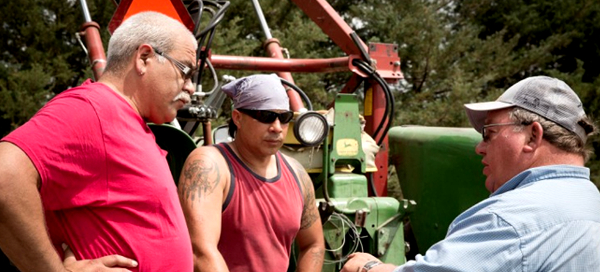 Amos Hinton and Mekasi Horinek of the Ponca Tribe of Oklahoma talk with farmer Art Tanderup during the 2014 planting of sacred Ponca corn on the Tanderup farm. (photo: Mary Anne Andrei)