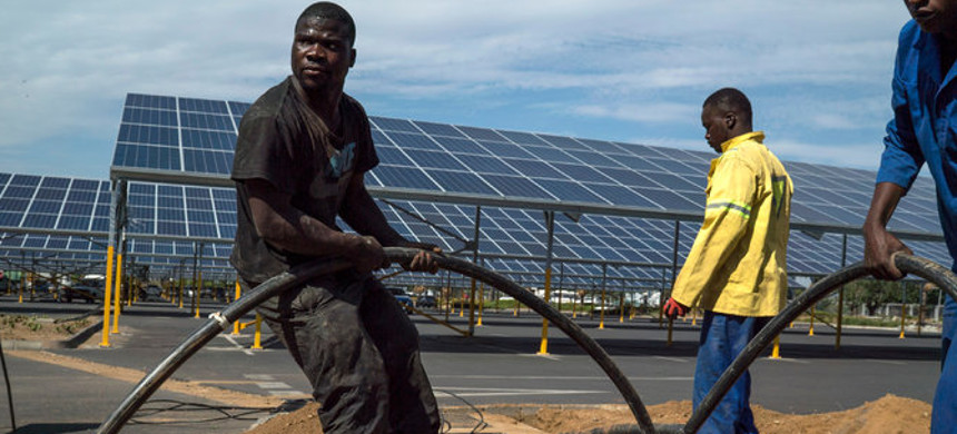 Workers laying cables for solar panels in Woodmead, north of Johannesburg. Many countries in Africa are looking at solar and wind power to bolster generation capacity and replace older and dirtier energy sources. (photo: Joao Silva/The New York Times)