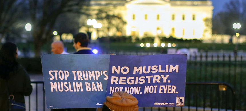 A person holds placards during a protest against Trump's revised travel ban in March. (photo: Erik S. Lesser/EPA)