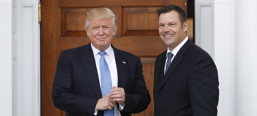 Kansas Secretary of State Kris Kobach, right, carries paperwork as he is greeted before a meeting with then president-elect Donald Trump at the Trump National Golf Club Bedminster clubhouse in Bedminster, New Jersey. (photo: Carolyn Kaster/AP)
