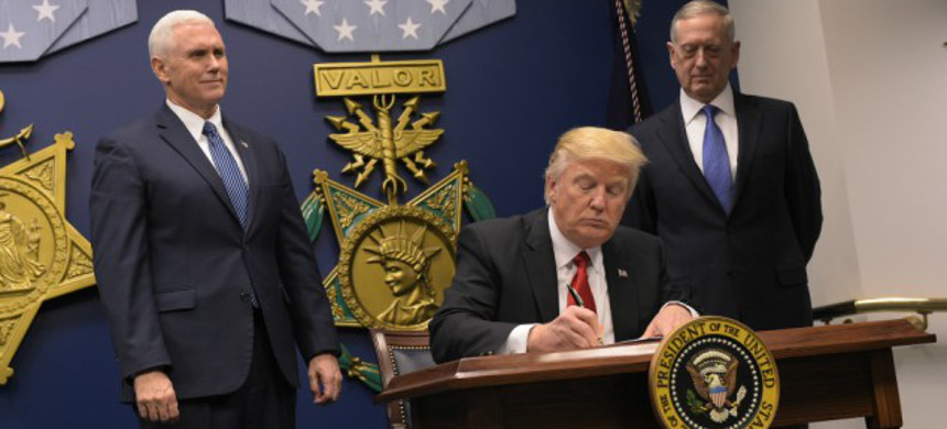 President Trump signs the original Muslim ban. (photo: Getty)