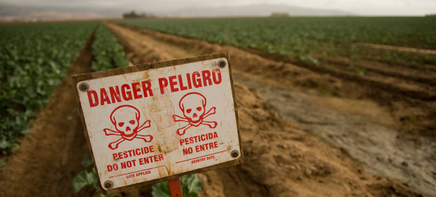 Farm fields with pesticides warning. (photo: Food and Environment Reporting Network)