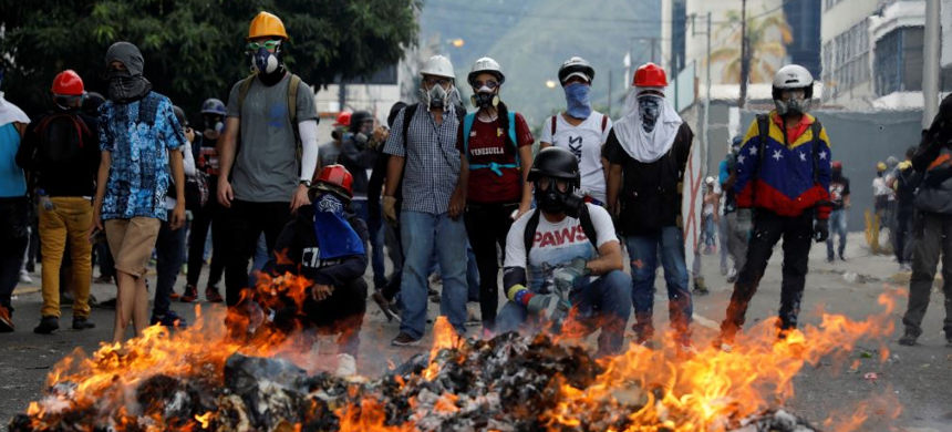 Opposition supporters stand in front of a fire during clashes with riot police at a rally against President Nicolas Maduro in Caracas, Venezuela. (photo: VOA News)