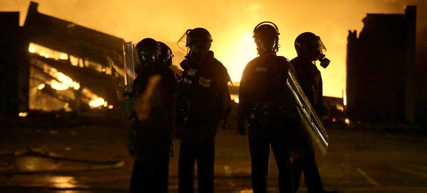 Police officers stand by as buildings are set on fire after the announcement of the grand jury decision, Nov. 24, 2014, in Ferguson, Mo. (photo:  Charles Riedel/AP)