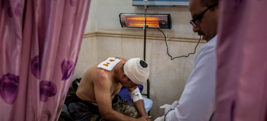 A doctor tends to a soldier injured in fighting in Qaraqosh in Mosul, Iraq. (photo: Chris McGrath/Getty)