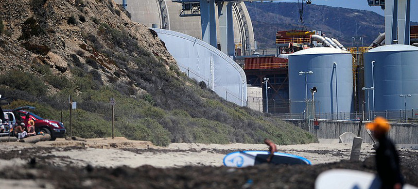 Surfers walk along a beach nearby the San Onofre nuclear power plant. (photo: AP)