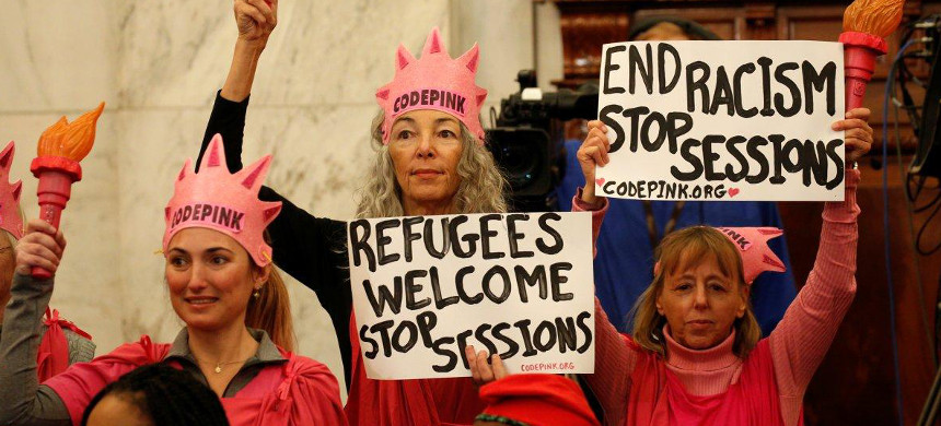 Protesters hold signs at the Senate Judiciary Committee confirmation hearing for U.S. senator Jeff Sessions. (photo: Kevin Lamarque/Reuters)