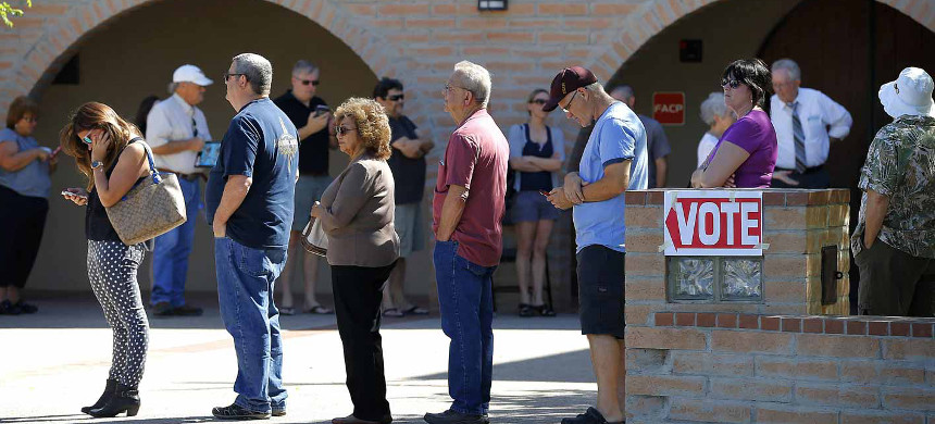 Voters stand in line to cast their ballots. (photo: AP)