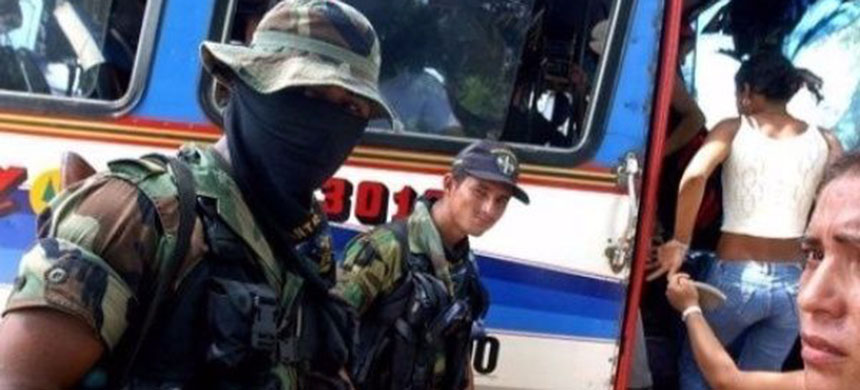 Members of the right-wing paramilitary group the United Self-Defense Forces of Colombia inspect a bus. (photo: EFE)