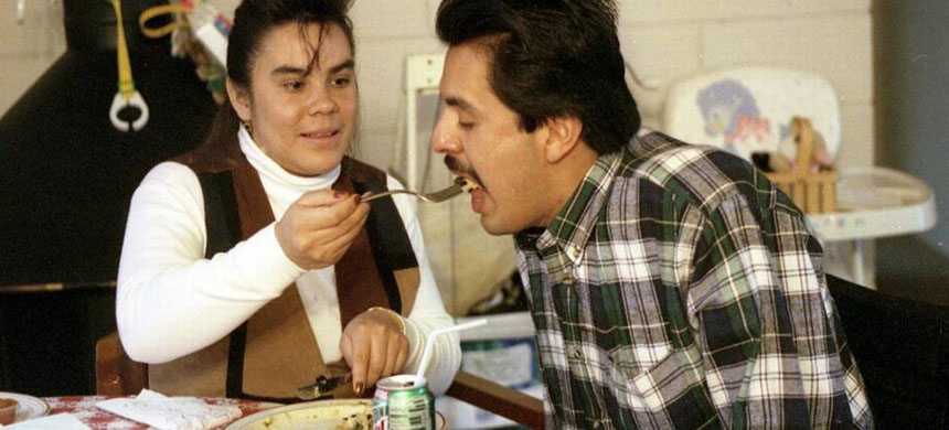 Javier Tellez Juarez' wife, Norma, feeds him in this December 1996 photo. He lost his limbs when his shirt was caught in machinery while he dug a post hole. An artificial arm allowed him to write, paint and eat a little bit, but his wife took over feeding him most of the time. His case prompted a change in Idaho law to require that farmers to carry worker's compensation insurance for their laborers. (photo: Katherine Jones/IdahoStatesman/McClatchy)
