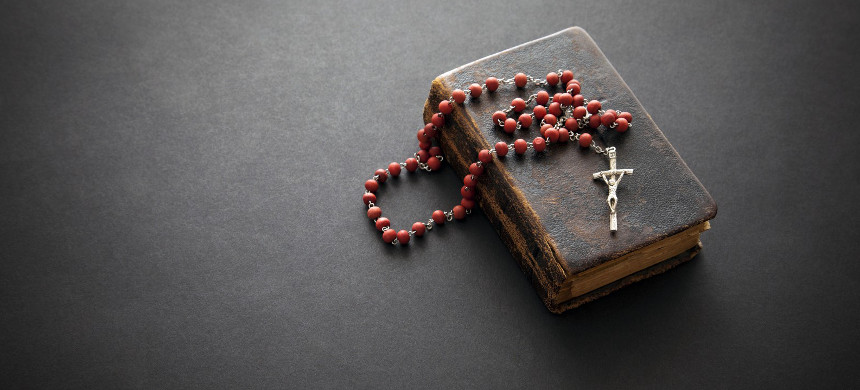 A rosary lays across a bible. (photo: iStock)