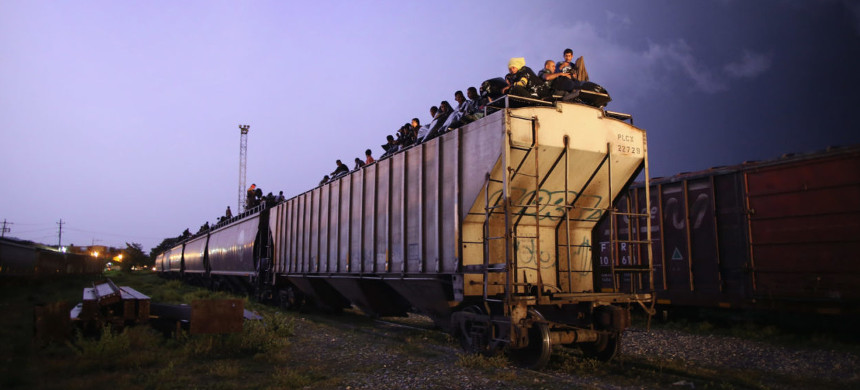 Central American migrants sit atop a freight train - known as 'La Bestia' - as it passes through Arriaga, Mexico, in 2013. (photo: John Moore/Getty)