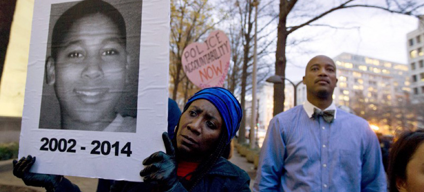 A protester holds a sign commemorating slain Tamir Rice. (photo: Jose Luis Magana/AP)