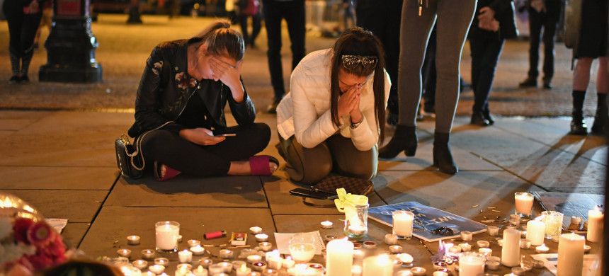 Women sit by a memorial set up for the victims of the Manchester terror attack. (photo: Getty)
