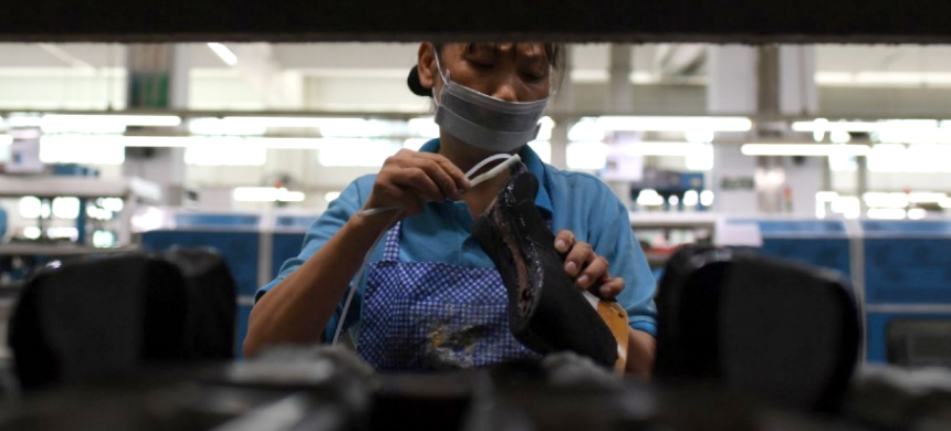 A worker puts glue on shoes at the Huajian shoe factory, where about 100,000 pairs of Ivanka Trump-brand shoes have been made over the years, in Dongguan, in south China's Guangdong province. (photo: Greg Baker/Getty Images)