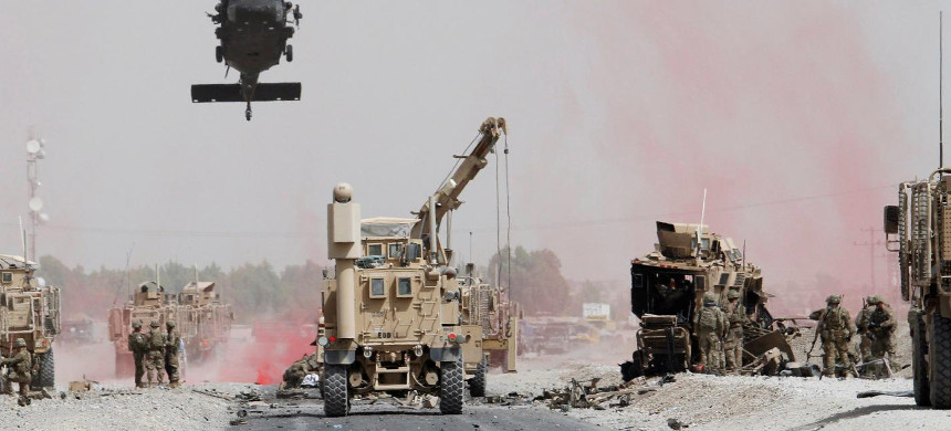 U.S. troops assess the damage to an armored vehicle of the NATO-led military coalition after a suicide bomber's attack in Kandahar province, Afghanistan, on August 2. (photo: Ahmad Nadeem/Reuters)