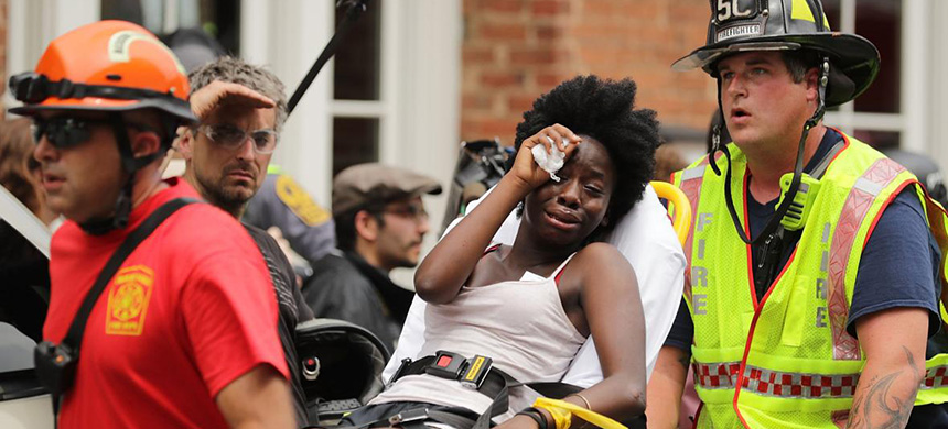 Rescue workers move victims on stretchers after a car plowed through a crowd of counterdemonstrators marching through the downtown shopping district Saturday in Charlottesville, Virginia. (photo: Getty Images)