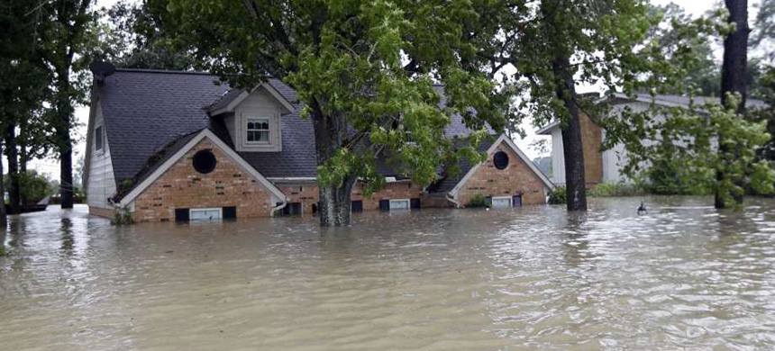 A home is surrounded by floodwaters from Tropical Storm Harvey, August 28, 2017, in Spring, Texas. (photo: David J. Phillip/AP)